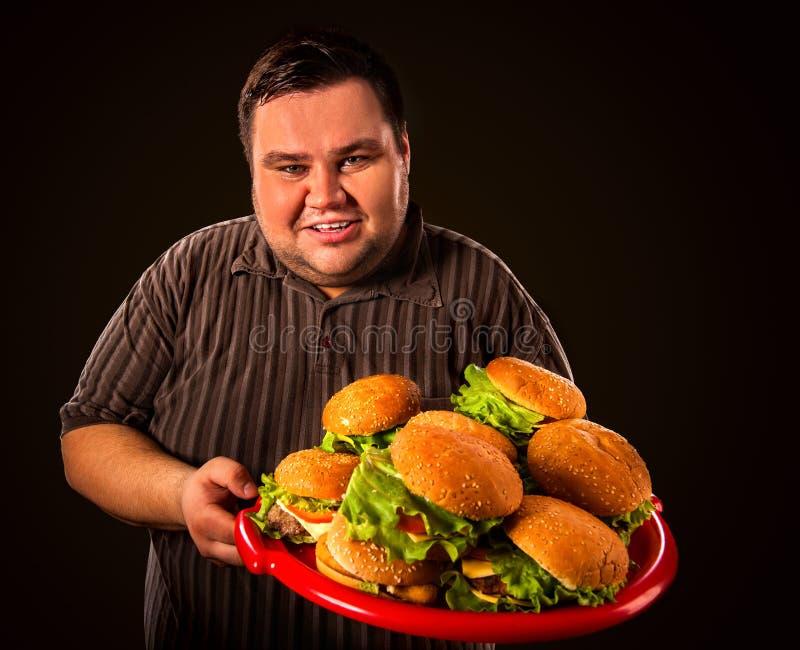 肥胖食人的快餐hamberger 超重人的早餐 免版税库存照片