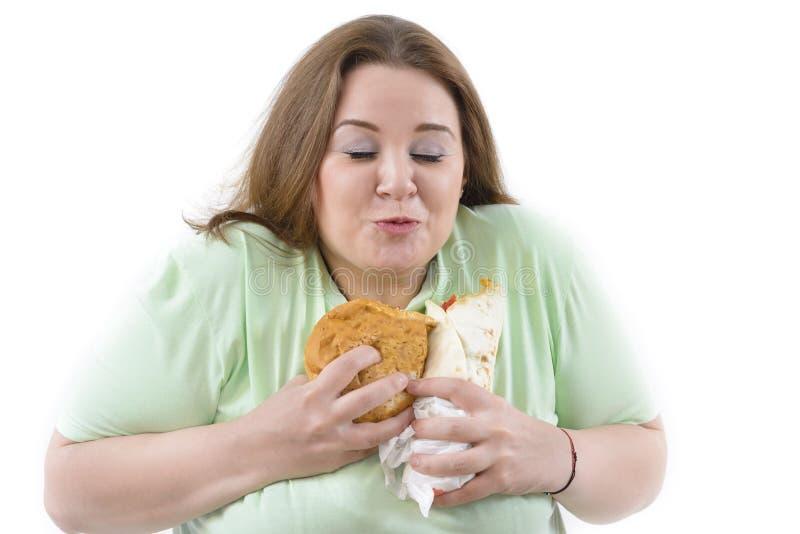 肥头大耳的妇女有瘾对不健康的食物 库存照片