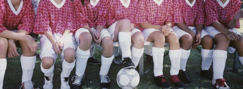 肩并肩坐女性的足球运动员 免版税库存图片