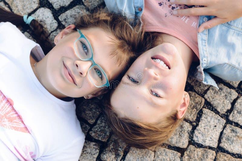 肩并肩说谎在与开放的眼睛和他们的头的地面上的两个年轻白肤金发的女孩 免版税图库摄影