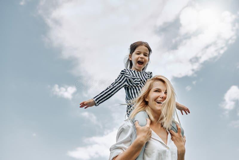 肩扛乘驾的愉快的矮小的滑稽的女儿与她天空背景的愉快的母亲 爱的妇女和她的女孩 库存图片