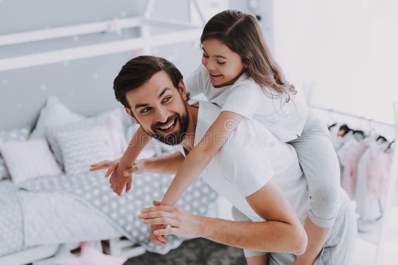 肩扛乘驾的逗人喜爱的年轻女儿与爸爸 免版税库存照片