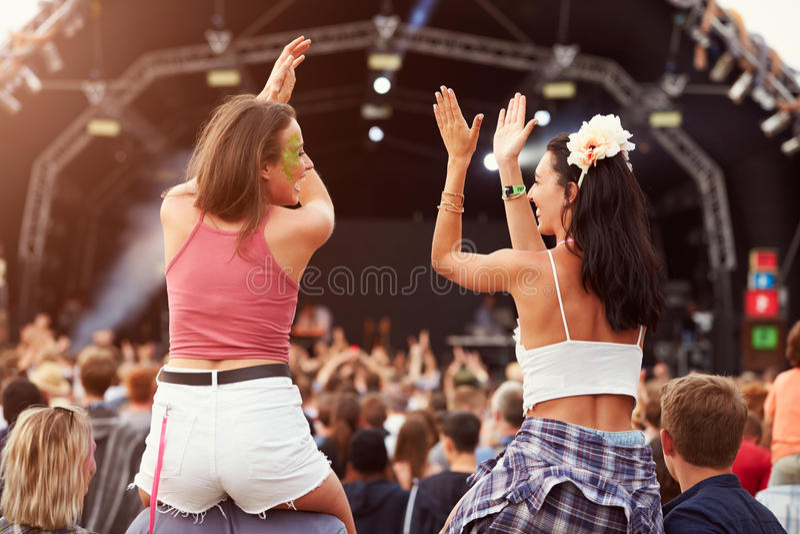 肩膀的两个女孩在音乐节的人群 库存照片