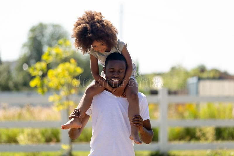 肩膀的微笑的非裔美国人的人运载的女儿 免版税库存照片