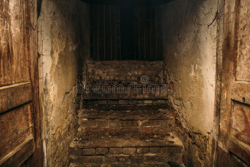 肮脏的从无家可归的人居住的被放弃的地下室,地方的难看的东西蠕动的木楼梯,退出到黑暗的街道 库存图片