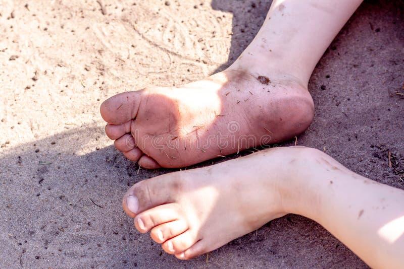 肮脏的儿童脚的假日概念在肮脏的土壤的 免版税库存照片