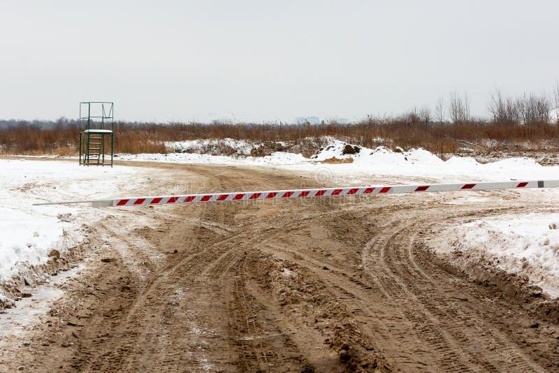 肮脏的冬天路,由关闭入口的障碍阻拦了 免版税库存图片