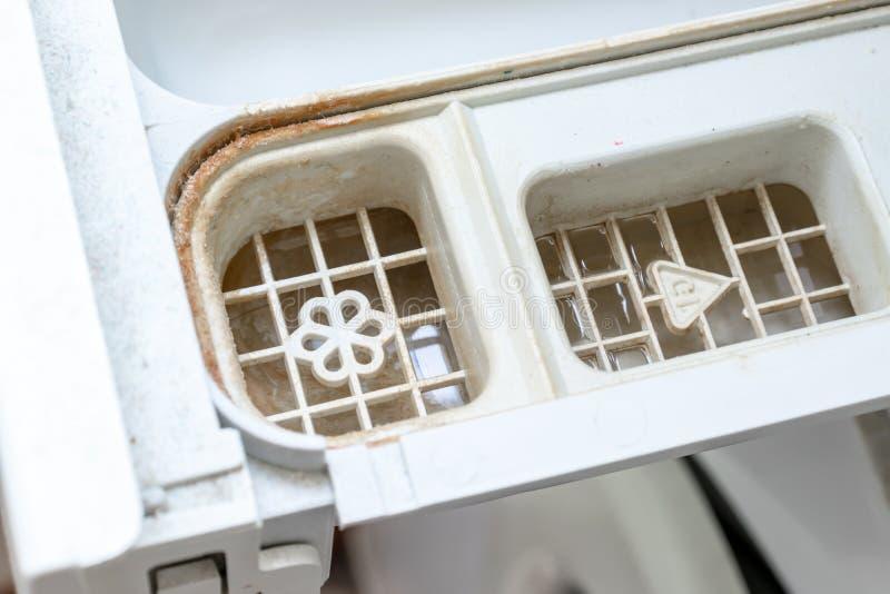肮脏的发霉的洗衣机洗涤剂和织品调节剂分配器抽屉隔间关闭 模子、铁锈和limescale 库存图片