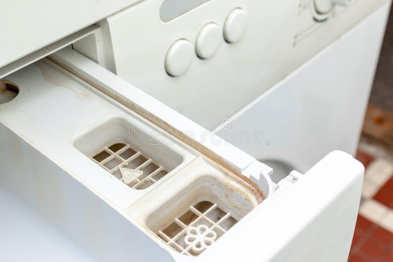 肮脏的发霉的洗衣机洗涤剂和织品调节剂分配器抽屉隔间关闭 模子、铁锈和limescale 免版税库存图片