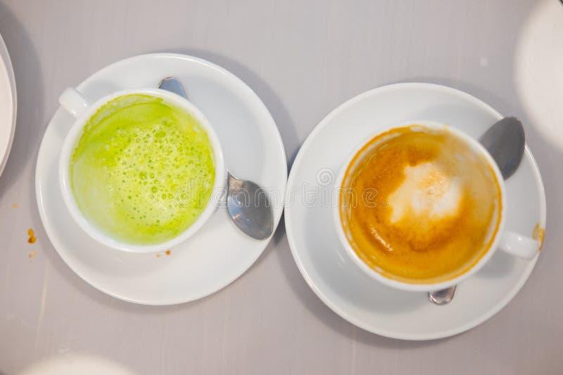 肮脏的咖啡和绿茶杯子的关闭 免版税库存照片