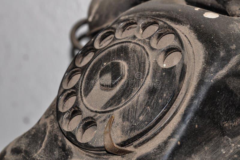 肮脏的多灰尘的黑老电话在车间 库存图片