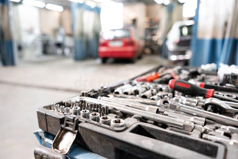 肮脏的套手在箱子的工具和wrenchs特写镜头 车库绘画汽车服务 用工具加工修理汽车或替换 免版税库存照片