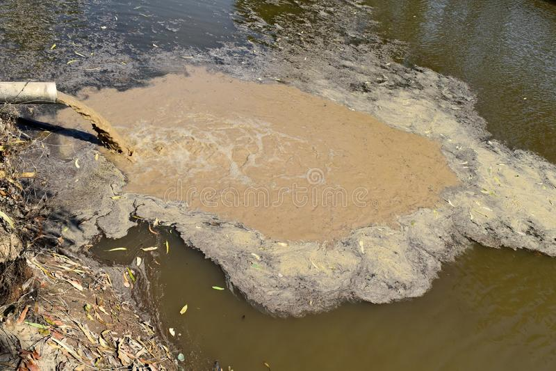 肮脏的水通过管子下落在水中 免版税图库摄影