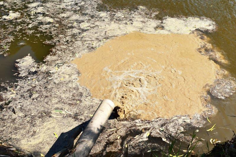 肮脏的水通过管子下落在水中 库存照片