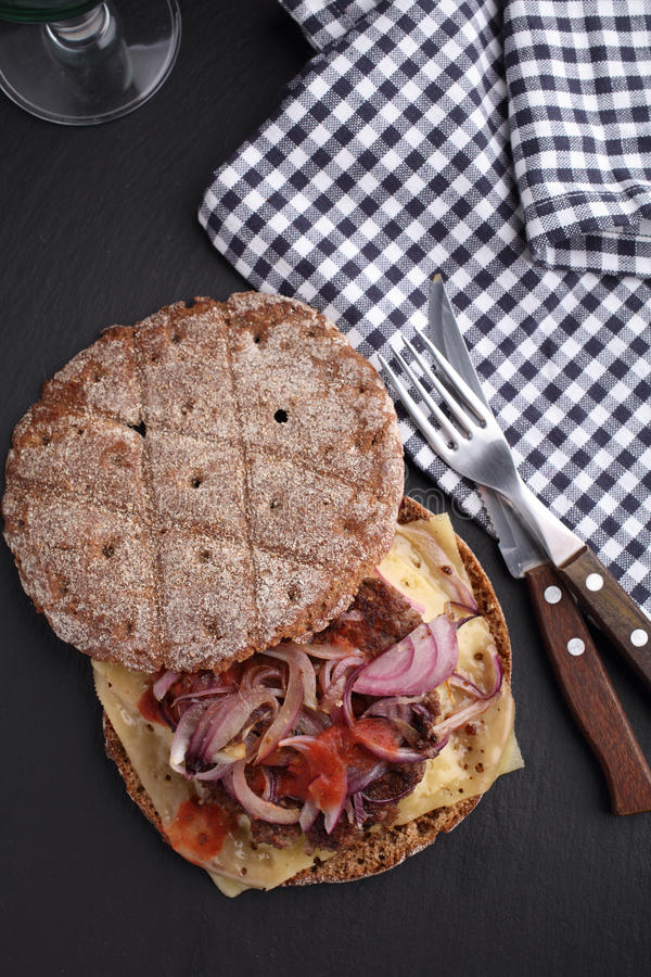 肮脏的汉堡用黑麦小圆面包 免版税库存照片