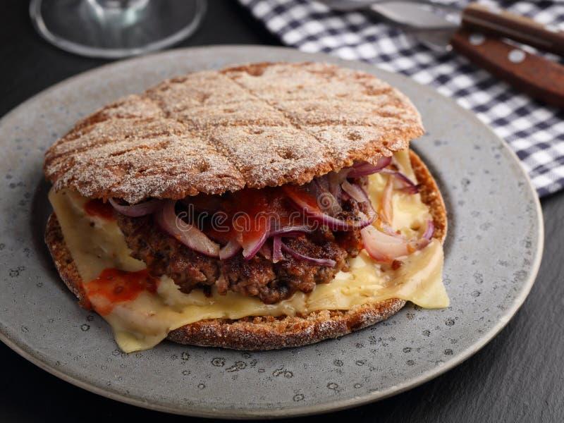 肮脏的汉堡用黑麦小圆面包 免版税图库摄影