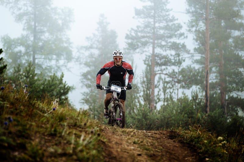 肮脏的男性骑自行车者沿小山上面乘坐 库存照片