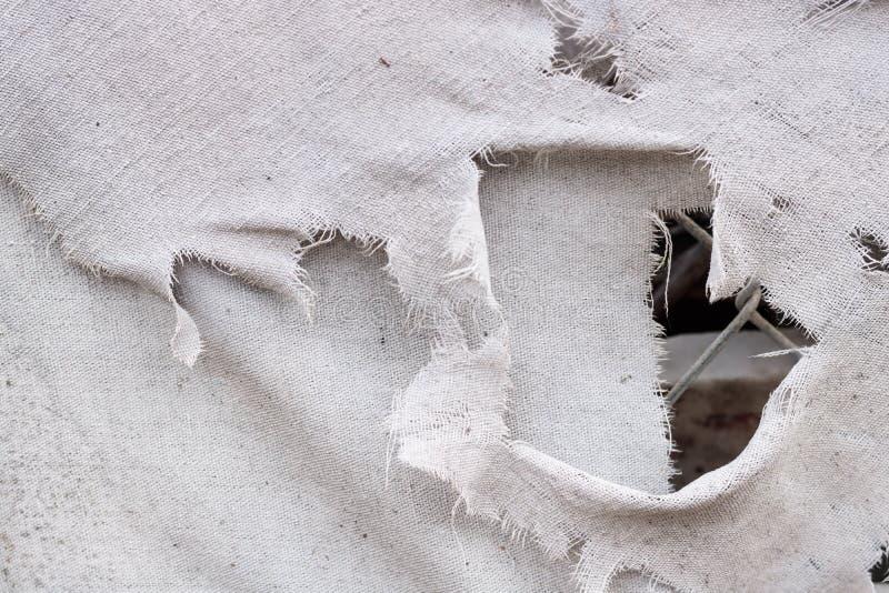 肮脏的白色灰色被撕毁的难看的东西葡萄酒织品帆布背景纹理,当链节看通过孔 免版税库存照片