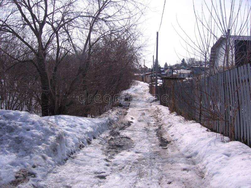 肮脏的胡同在一个被放弃的西伯利亚村庄 免版税库存图片