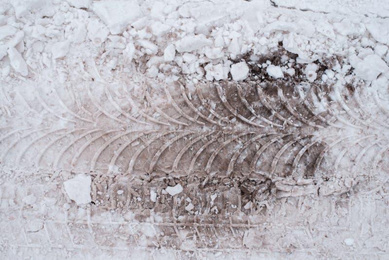 肮脏的雪特写镜头在冬天在城市 汽车` s的轮子的踪影在雪践踏 免版税图库摄影