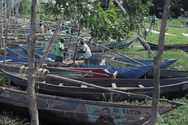 肯尼亚,基苏木- 2017年5月20日:两准备他的小船的非洲人在工作前 洗澡的人们在湖 免版税库存照片
