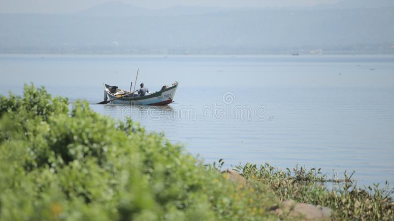 肯尼亚,基苏木- 2017年5月20日:单独荡桨非洲的人坐在小船和 渔夫在海工作 免版税图库摄影