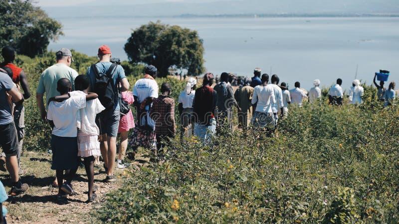 肯尼亚,基苏木- 2017年5月20日:大小组非洲和白种人人民一起去海的岸 库存图片