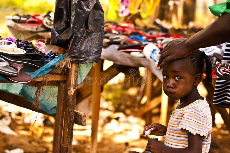 肯尼亚mara马塞语 2011年12月18日:肯尼亚女孩在与她的母亲的一个市场上在Mombassa 免版税库存图片