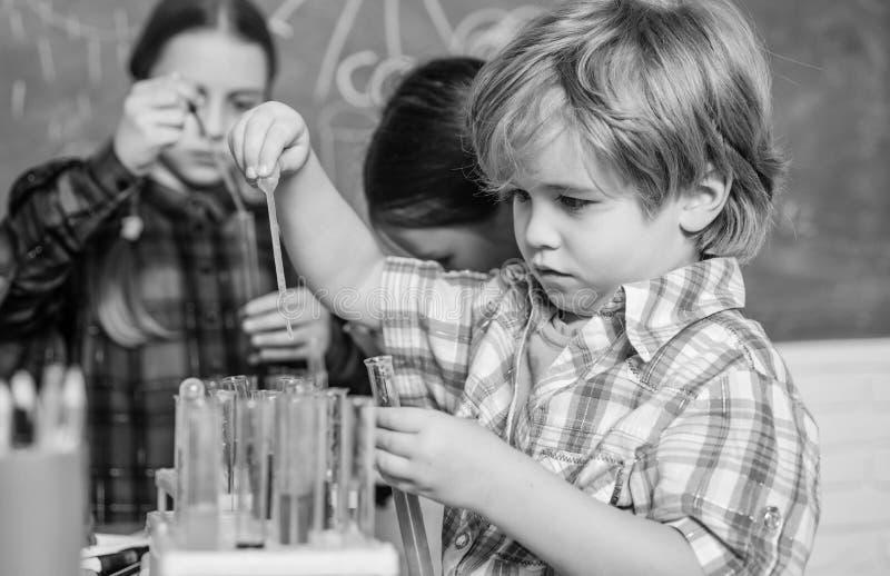 育儿和发展 t 孩子可爱的朋友获得乐趣在学校 学校化学实验室概念 免版税库存图片