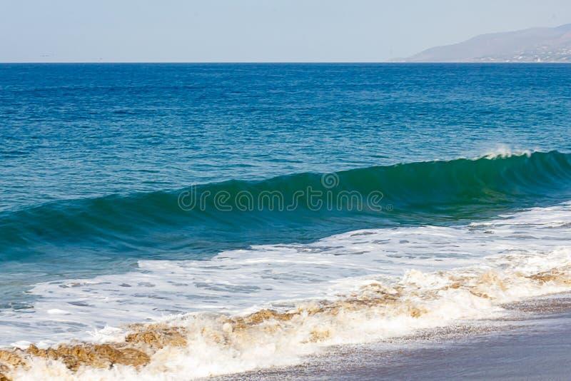 胀大与起泡沫的回流的torqpiose波浪,在海洋浩瀚对天际,小山, 免版税库存照片
