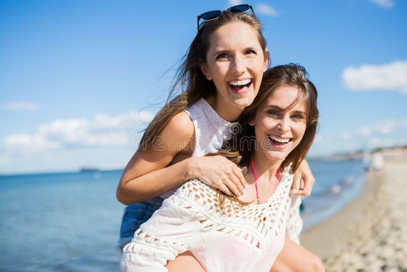 背上乘坐在她的最好的朋友的愉快的妇女 库存图片