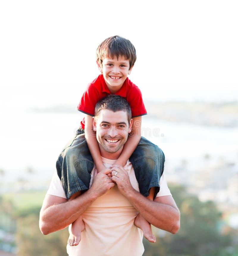 背上产生乘驾儿子的父亲 免版税图库摄影
