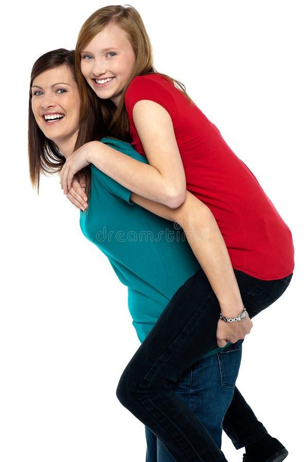 背上产生乘驾的愉快的母亲她的女儿 库存图片