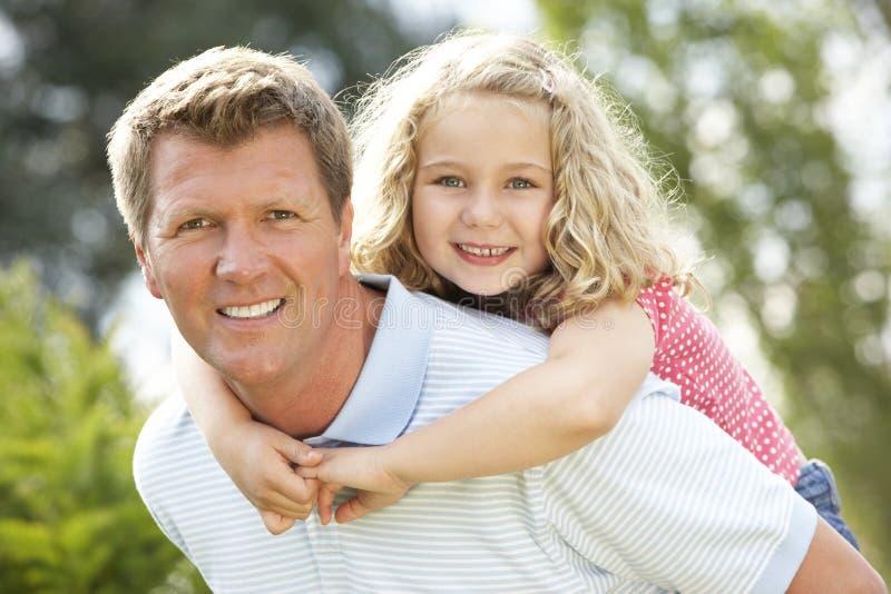 背上产生女儿的父亲 免版税库存图片