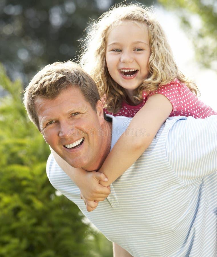 背上产生女儿的父亲 库存照片
