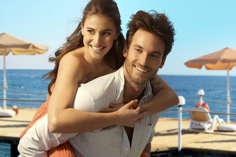 背上使用在海边海滩的愉快的夫妇 免版税图库摄影