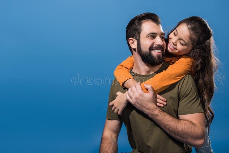 背上给可爱的女儿的英俊的父亲 免版税库存图片
