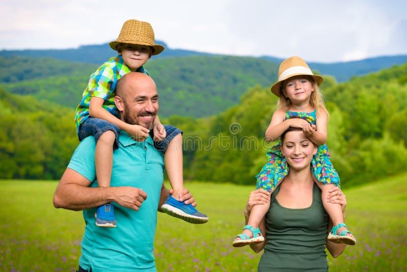 背上给乘驾孩子,愉快的家庭的父母 免版税库存照片