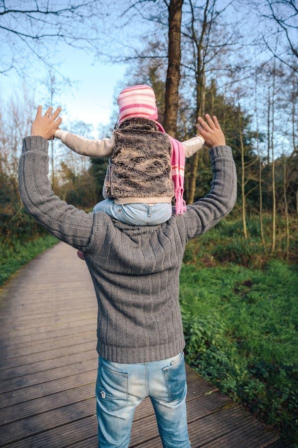 背上给乘驾的人小女孩在森林里 免版税库存图片