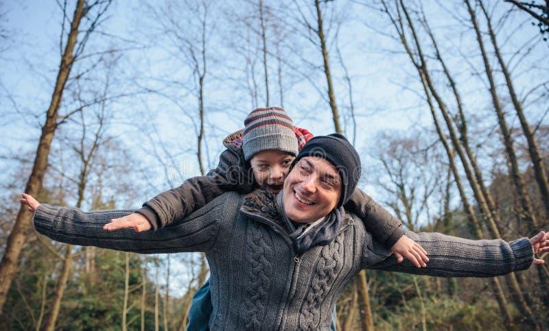 背上给乘驾的人愉快的孩子在森林里 免版税库存图片