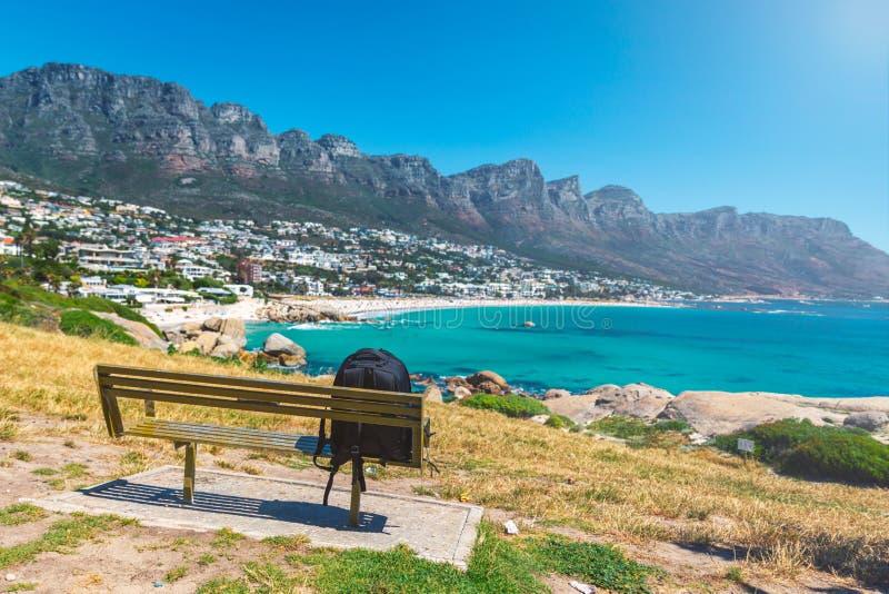 背包一条长凳的孤独的旅行家以阵营为目的在开普敦咆哮美丽的海滩 免版税库存图片