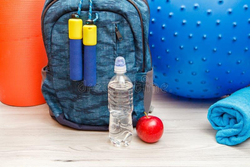背包和不同的工具为健身在地板上在屋子里 库存图片