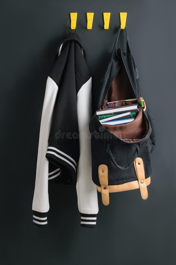 背包和夹克在墙壁上 库存照片
