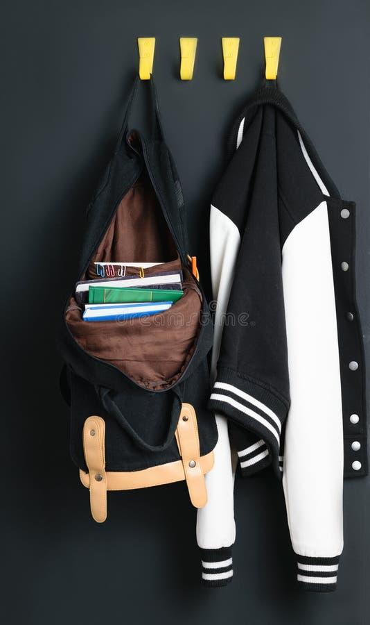背包和夹克在墙壁上 免版税库存照片