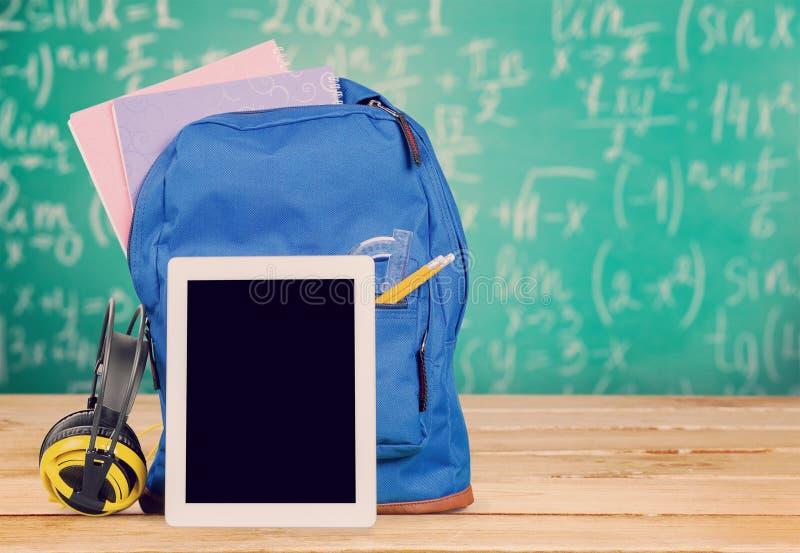 背包和数字式片剂在桌上 免版税库存图片