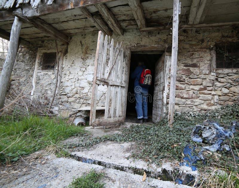 背包徒步旅行者在北意大利进入老被放弃的槽枥在 免版税库存照片