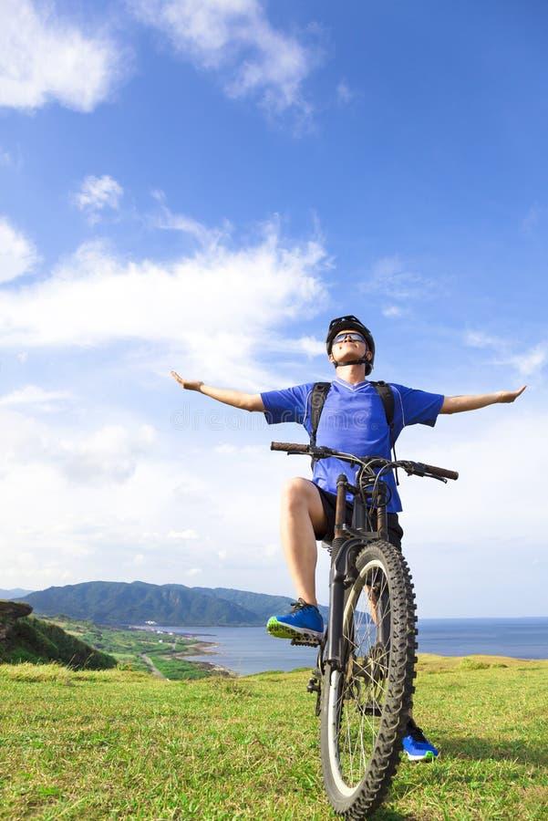 年轻背包徒步旅行者坐登山车和松弛姿势 免版税库存图片
