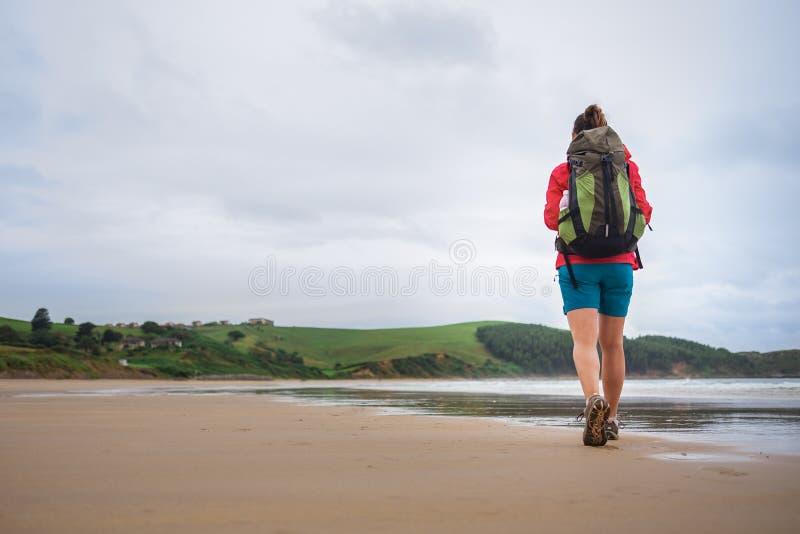 背包徒步旅行者女孩在离开的旅客步行ocen海滩 免版税库存图片