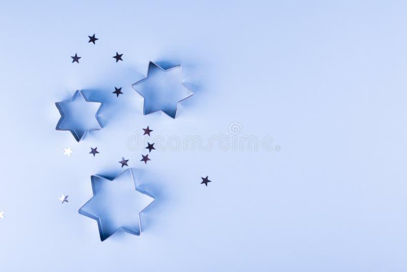 背景上色节假日红色黄色 小组在蓝色淡色背景的小的银色星 顶视图 免版税库存图片