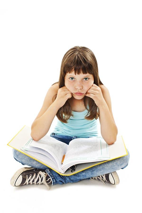 背景下来难倒沮丧的坐女孩家庭作业被淹没的学校学习疲乏的空白年轻人 女孩下来坐地板 免版税库存照片